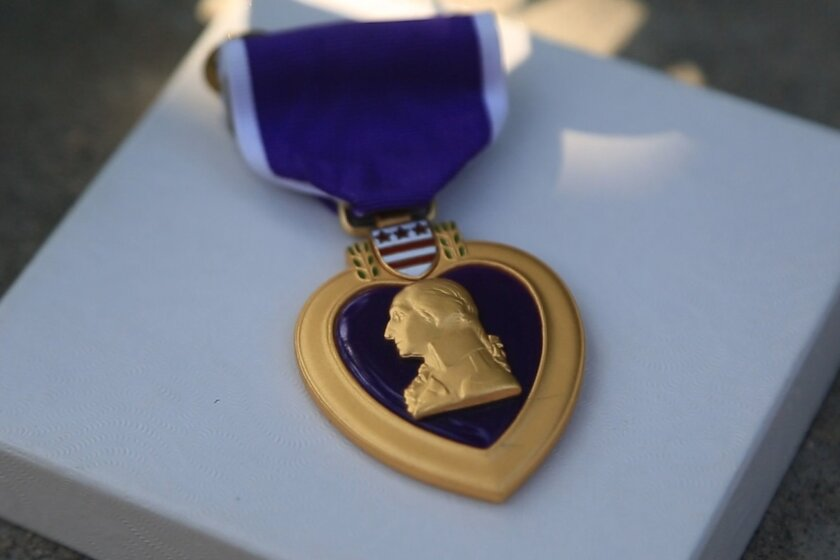 A Purple Heart medal was among the items left the police memorial downtown honoring slain Officer Jonathan De Guzman.
