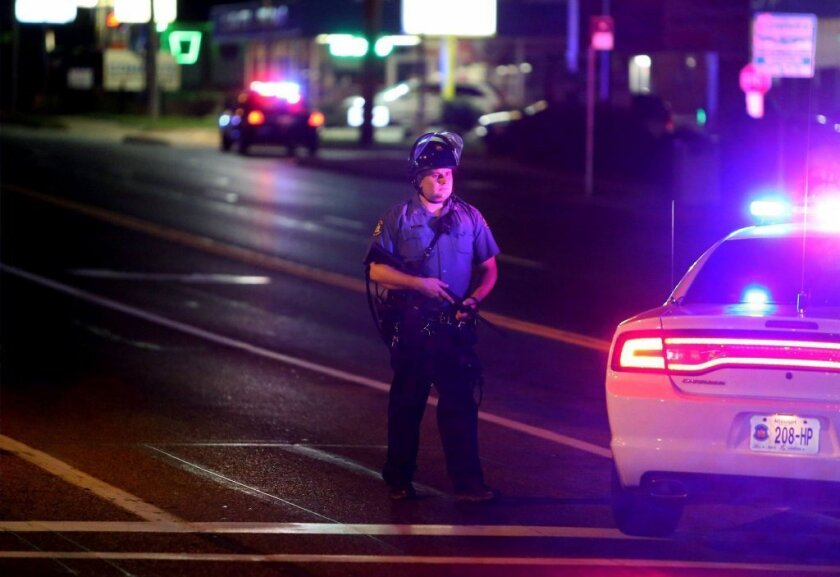 An officer guards a road after a Ferguson, Mo., police officer was shot in the arm Saturday night.