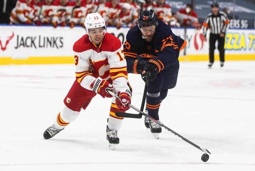 Edmonton Oilers' Leon Draisaitl (29) chases Calgary Flames' Johnny Gaudreau (13) during the third period of an NHL hockey game Saturday, May 1, 2021, in Edmonton, Alberta. (Jason Franson/The Canadian Press via AP)