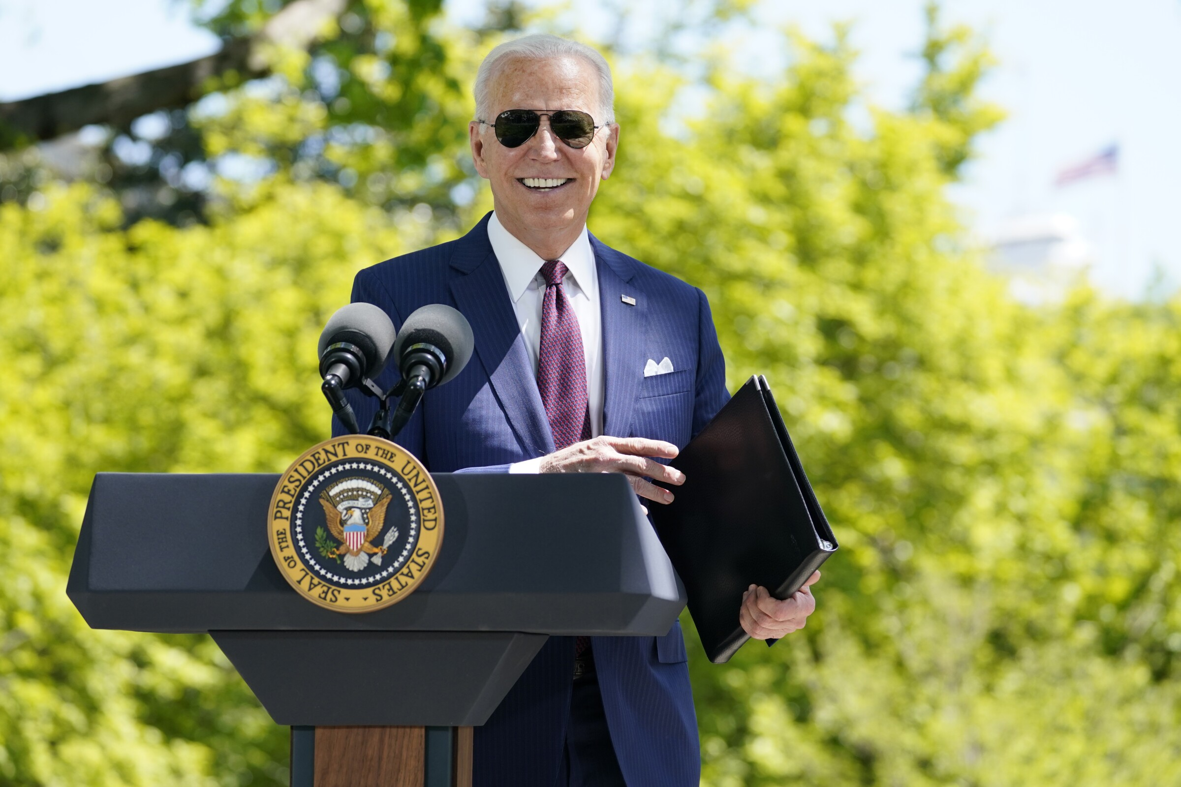 President Biden smiles as he stands behind a podium on the North Lawn of the White House
