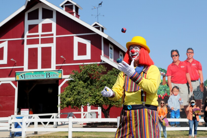 Fair clown VeeKay juggles as he entertains fairgoers as they enter the main entrance during opening day at the O.C. Fair.