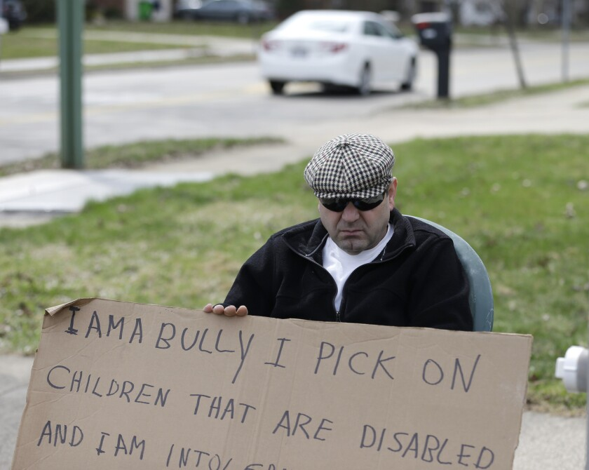 Edmond Aviv sits on a street corner holding a in South Euclid, Ohio declaring he's a bully, a requirement of his sentence because he was accused of harassing a neighbor and her disabled children for the past 15 years.