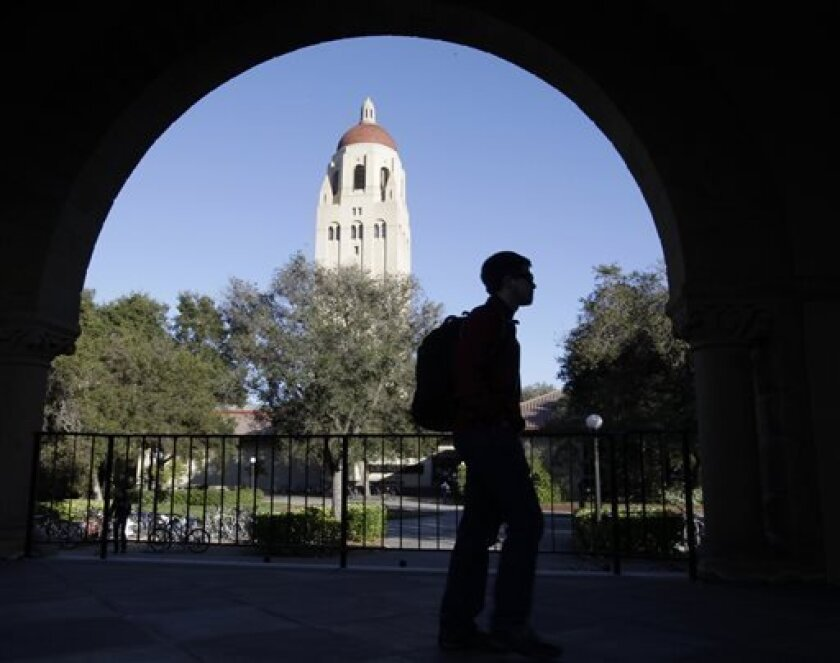 FILE - In this Feb. 15, 2012 file photo, a Stanford University student walks in front of Hoover Tower on the Stanford University campus in Palo Alto, Calif. Congressional inaction could end up costing college students an extra $5,000 on their new loans. The rate for subsidized Stafford loans is set