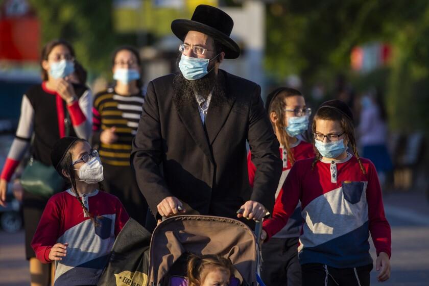 Judíos ultraortodoxos esperan a cruzar una carretera cerrada y llegar a sus casas, equipados con mascarillas para combatir los contagios del coronavirus en Ashdod, Israel, el jueves 2 de julio de 2020. (AP Foto/Ariel Schalit)