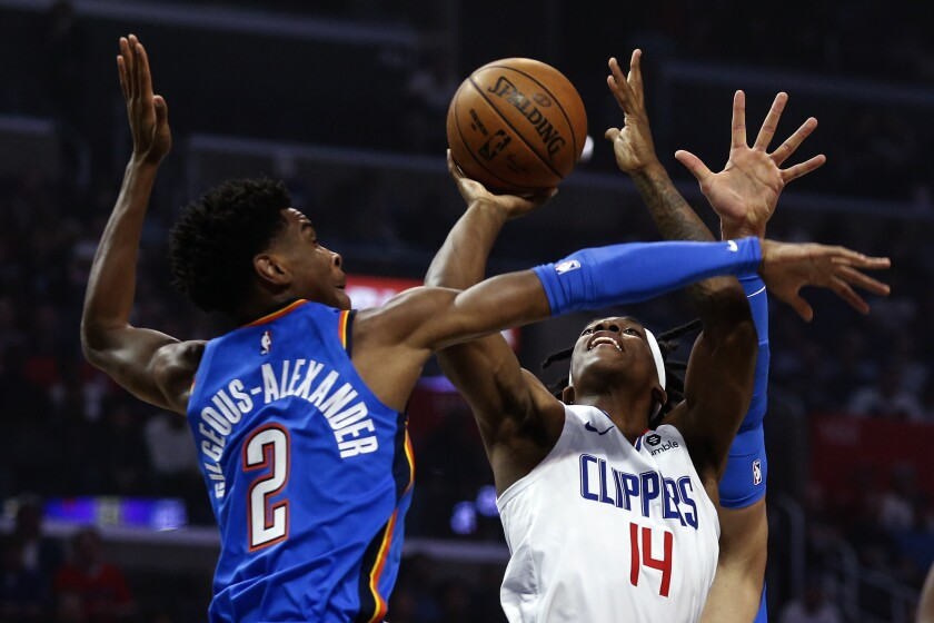 Clippers guard Terance Mann (14) shoots under pressure from Thunder guard Shai Gilgeous-Alexander (2) during the first half of a game Nov. 18 at Staples Center.