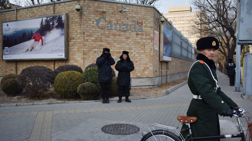 Chinese police stand guard outside the Canadian Embassy in Beijing on Monday.