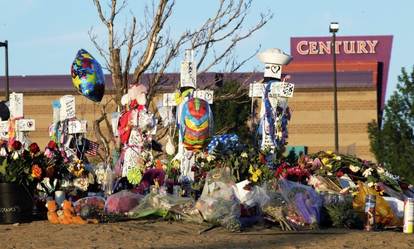 FILE - In this July 27, 2012 file photo, crosses, flowers and other mementos of the victims of the Aurora, Colo. movie theater shooting are shown at sunrise with the movie theater in the background. Jury selection begins Tuesday, Jan. 20, 2015, in the trial of accused gunman James Holmes in the sho