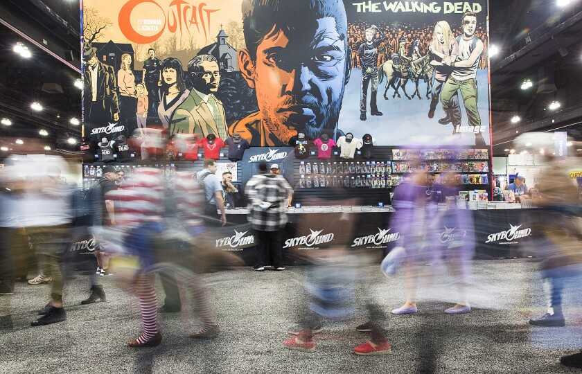 """WonderCon attendees walk past """"The Walking Dead"""" booth at the Los Angeles Convention Center."""