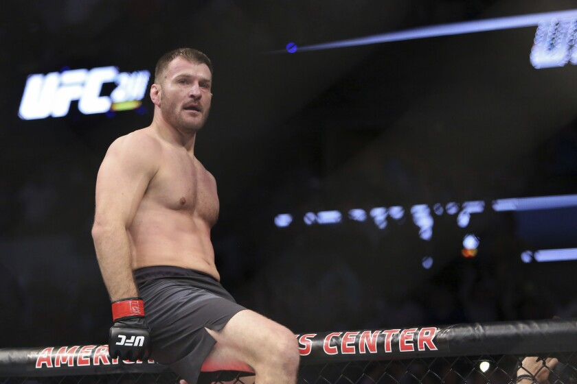 Stipe Miocic celebrates a win over Junior Dos Santos in a mixed martial arts bout at UFC 211 for the UFC heavyweight championship on May 13 in Dallas.