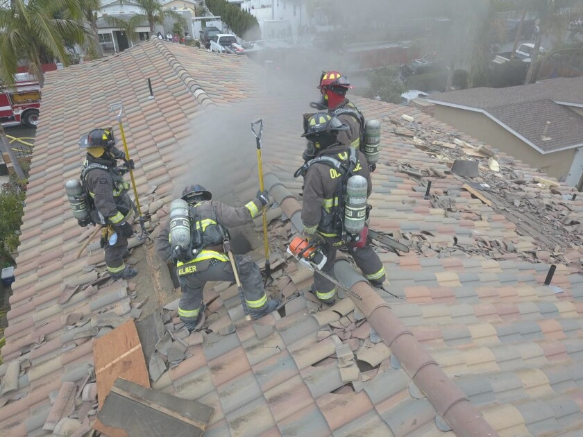 Oceanside firefighters work Monday to ventilate a home on Dubuque Street after cutting a hole in the roof.