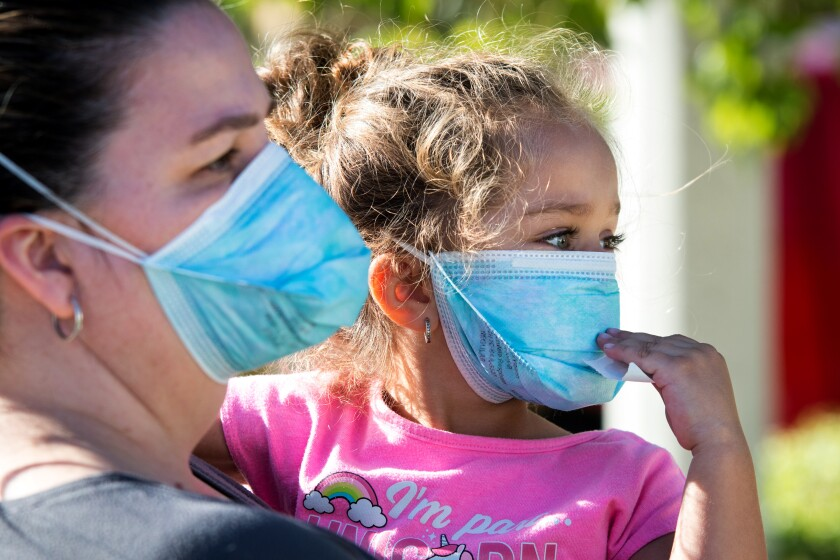 A mother and daughter, both evacuees of the Tick fire near Santa Clarita, wear respirator masks.