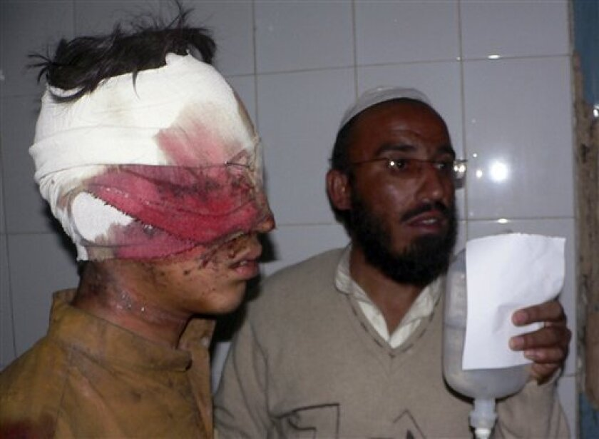 An injured victim of a suicide bombing is helped by an identified man upon his arrival at a local hospital in Bannu, Pakistan on Friday, Jan. 1, 2010. A suicide bomber set off an explosives-laden vehicle on a field during a volleyball tournament Friday in northwest Pakistan, killing scores of people and wounding dozens, police said. (AP Photo/Ijaz Muhammad)