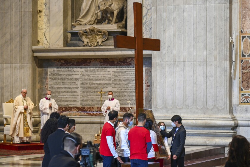 Pope Francis, left, watches as youths from Panama hand over the World Youth Day cross to youths from Portugal, at the end of a Mass celebrated on the occasion of the Christ the King festivity, in St. Peter's Basilica at the Vatican, Sunday, Nov. 22, 2020. The next World Youth Day will be held inPortugal in 2023. (Vincenzo Pinto/Pool via AP)