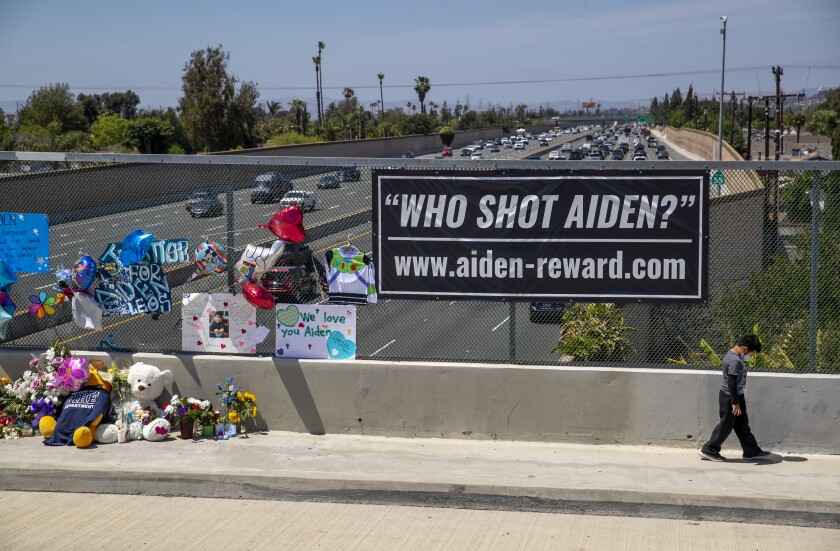"""A boy walks by a cluster of teddy bears, flowers and a sign that says """"Who shot Aiden?"""" on a bridge overlooking the freeway."""