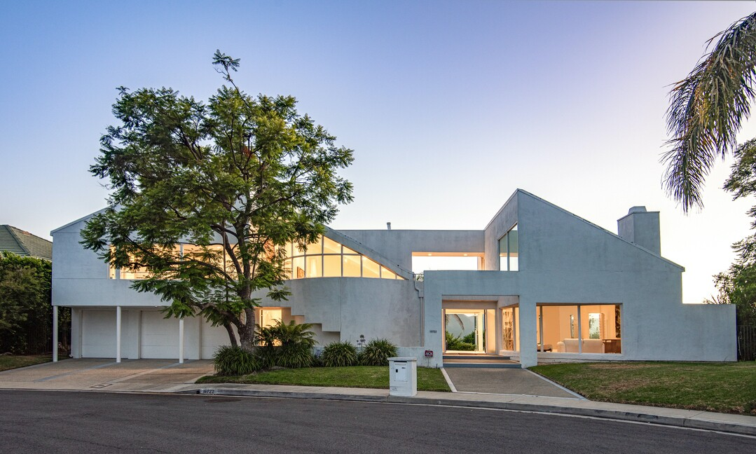 The modern home draws the eye with curving lines, sloping roofs and a sleek whitewashed exterior.