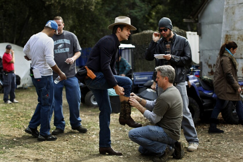 """Actor Timothy Olyphant (in the cowboy hat) as Deputy U.S. Marshal Raylan Givens, is prepared for his microphone before shooting begins on the """"Church of the Two-Stroke Jesus"""" set."""
