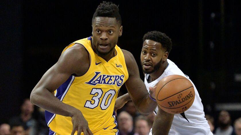 Lakers forward Julius Randle controls the ball against Memphis forward JaMychal Green on Jan. 15.