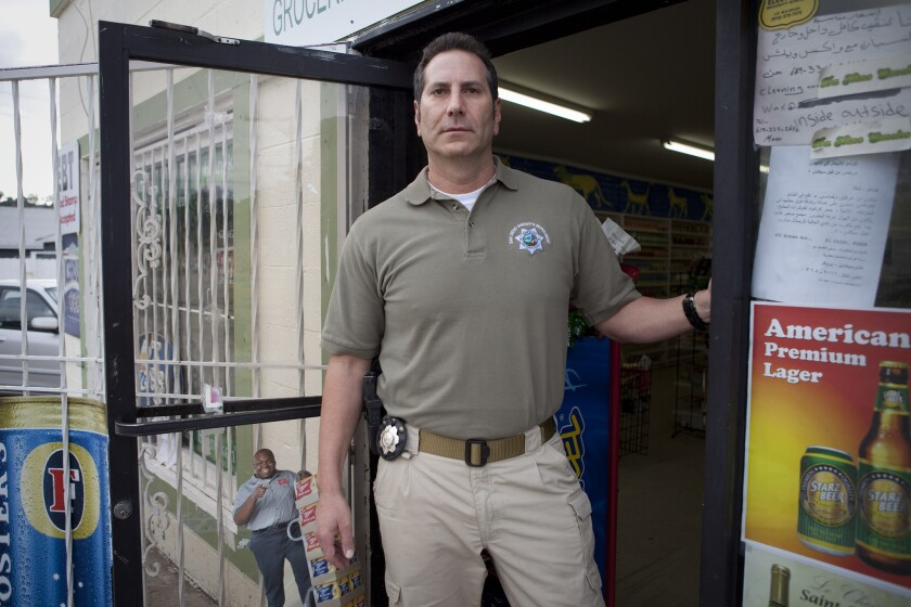 In this Union-Tribune file photo, then-sheriff's Lt. Marco Garmo stands at the El Cajon market that once belonged to his family.