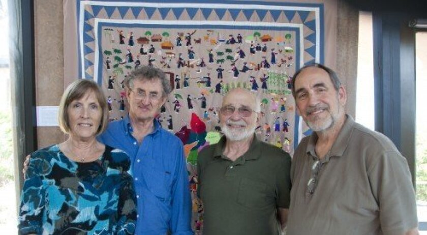 From left, Nancy Harmon, Roger Harmon, Irving Himelblau and Bob Montgomery stand in front of a Hmong story cloth. Photo: Claire Harlin