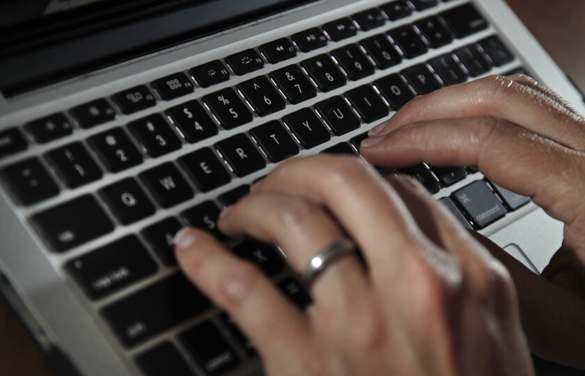 A person types on a laptop keyboard