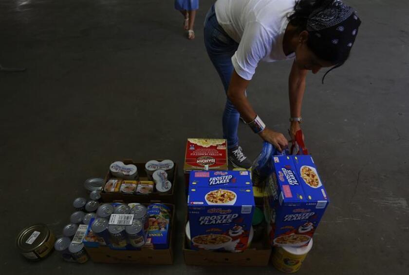 Voluntarios acomodan comida que será distribuida a las familias más necesitadas de Puerto Rico. EFE/Archivo