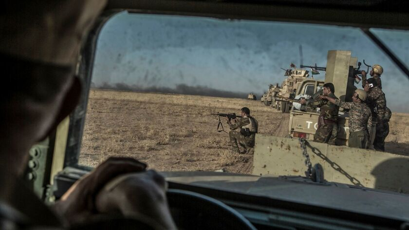 Peshmerga forces shoot during an operation to liberate several villages currently under the control of the Islamic State militant group southeast of Mosul, north Iraq.