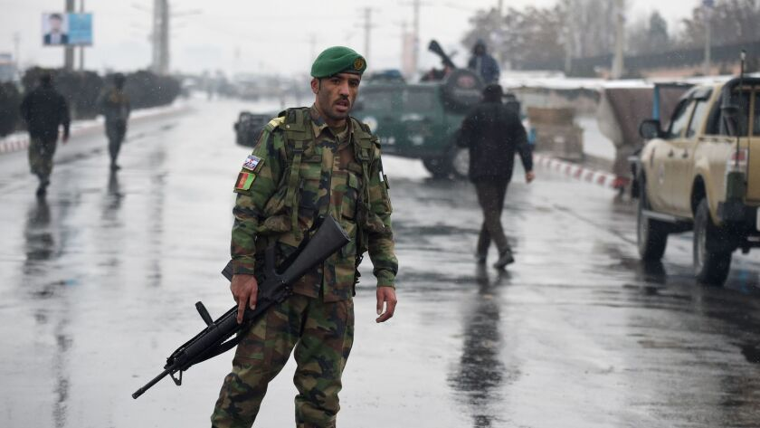 Afghan security personnel stand guard near the site of an attack on the Marshal Fahim National Defense University in Kabul on Jan. 29.