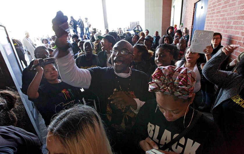 """A group of protesters chant """"Black lives matter"""" outside the West Oakland BART train station. Fourteen protesters were arrested after they formed a human chain on the platform."""