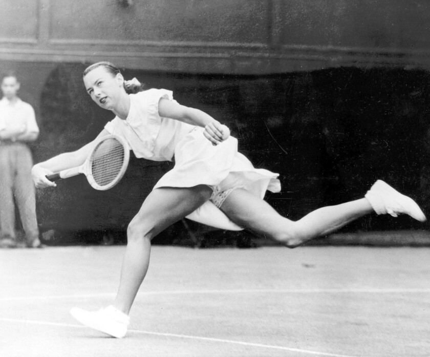 "Gertrude ""Gussy"" Moran races across Centre Court to make a return shot in third round women's singles match in Wimbledon, England, on June 22, 1949. Moran beat Betty Wilford of Britain, 6-2, 6-4. The American tennis player, from Santa Monica, wears a short tennis dress with ruffled, lace-trimmed briefs showing below the hem. The tennis outfit, designed and sewn by former tennis player-turned-fashion designer Teddy Tinling, earned her the nickname ""Gorgeous Gussey."""