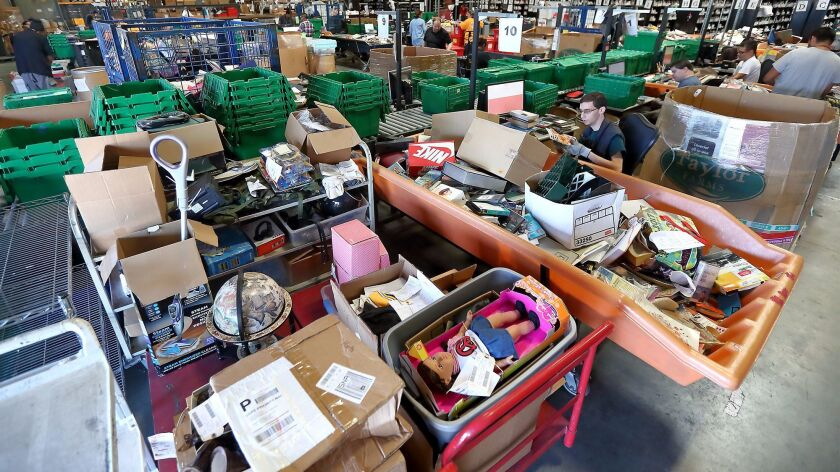 Program participants sort through and categorize donated items at a Goodwill of Orange County warehouse in Santa Ana.