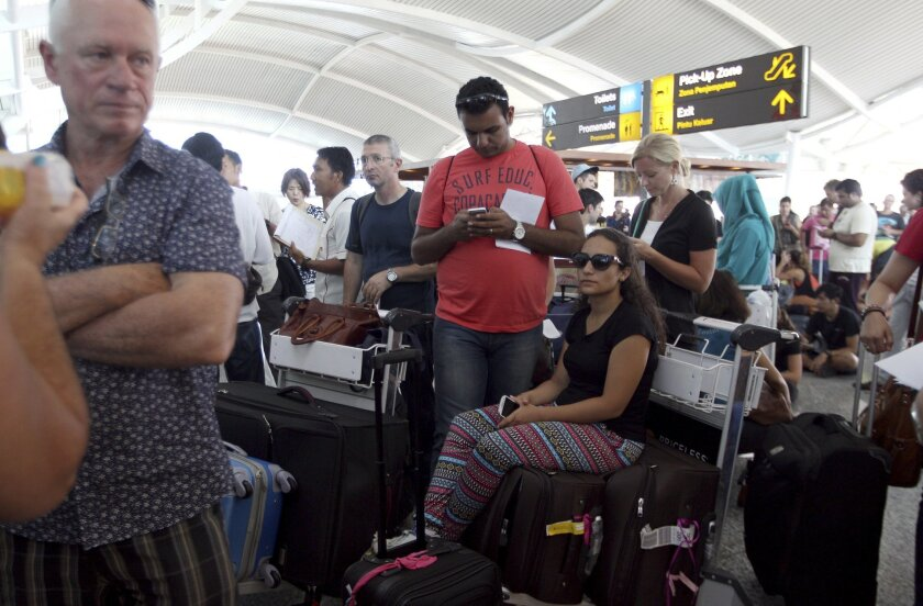 Passengers wait to check the status of their flights with airline desk at Ngurah Rai International Airport in Bali, Indonesia Wednesday, Nov. 4, 2015. Ash spewing from a rumbling volcano in eastern Indonesia blanketing villages with thick ash, forcing the closure of two airports and international a