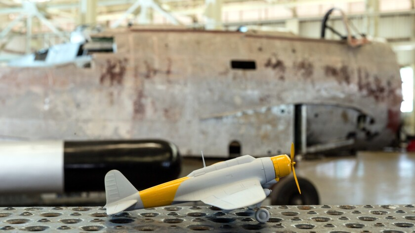 A model of the Japanese bomber nicknamed Kate sits near the remnants of one of the actual planes at the Pacific Aviation Museum Pearl Harbor, where it is being restored.