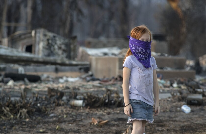Chloe Hoskins, 7, wearing a bandanna to protect herself from the smoke and ash, checks on a neighbor's burned-out property with her father in the Coffey Park neighborhood in Santa Rosa.