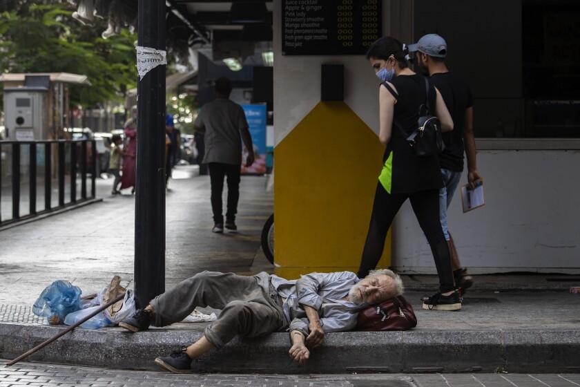 Una mujer mira a un hombre desamparado que duerme en la acera en la calle Hamra, en Beirut, el 17 de julio del 2020. El ministerio de economía de Líbano elevó el 22 de junio del 2021 el precio del pan subsidiado por quinta vez en un año, en momentos en que la economía del país empeora sin que se avizore el fin de la crisis. (AP Foto/Hassan Ammar)