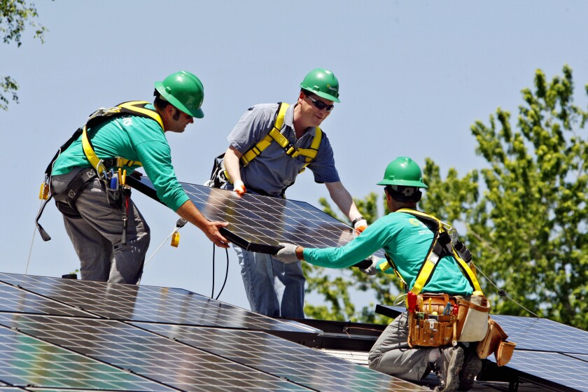 SolarCity workers install panels on a Denver home with Sen. Michael Bennet (D-Colo.), center, in 2010.