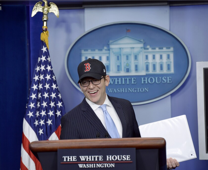 White House Press Secretary Jay Carney, wearing a Boston Red Sox baseball cap because the World Series champions were honored by the president, begins the daily briefing, where he announced that more than 7 million people have signed up for Obamacare.
