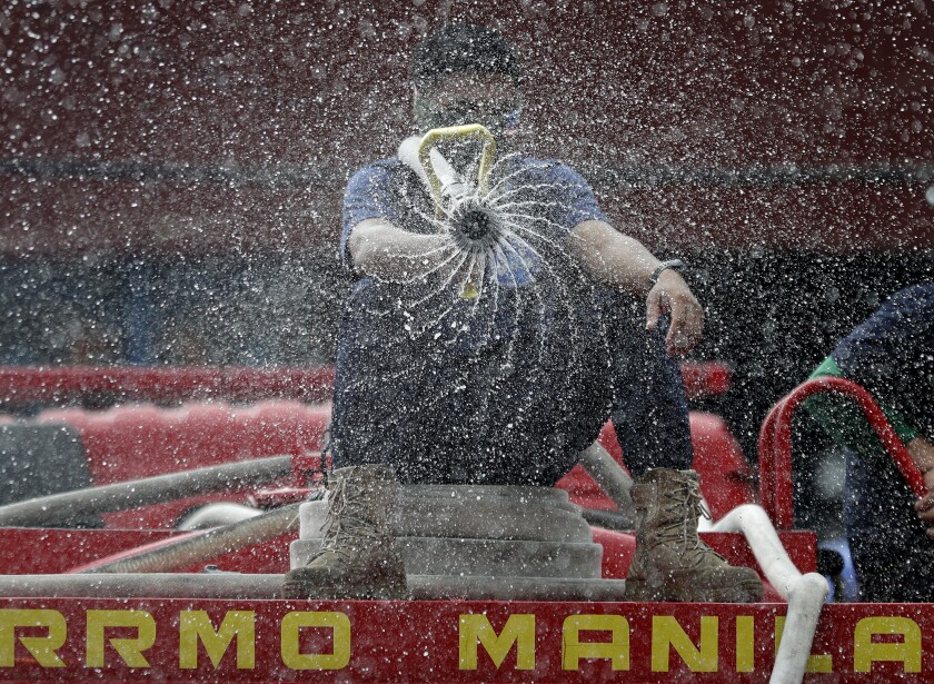 Firemen spray disinfectants outside a public market in Manila, Philippines on Wednesday, March 11, 2020. For most people, the new coronavirus causes only mild or moderate symptoms, such as fever and cough. For some, especially older adults and people with existing health problems, it can cause more severe illness, including pneumonia. (AP Photo/Aaron Favila)