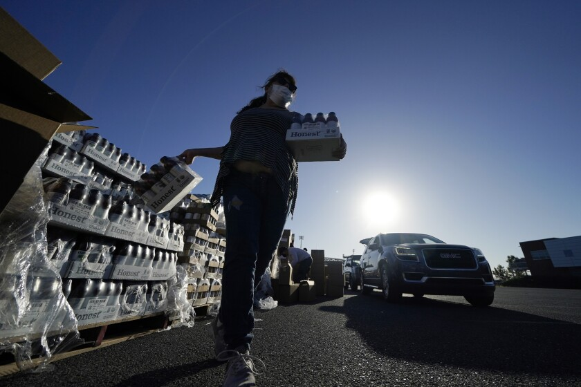 Volunteers distribute food to people who waited in line in their cars overnight, at a food distribution point in Metairie, La., Thursday, Nov. 19, 2020. (AP Photo/Gerald Herbert)