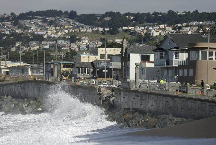 FILE - In this file photo from Monday, Jan. 25, 2016, waves crash near a damaged section of seawall in Pacifica, Calif. Living with the Pacific Ocean as your backyard has its benefits. But the crumbling ocean cliffs have forced dozens to move quickly and at a high cost. Still, others remain, unsure