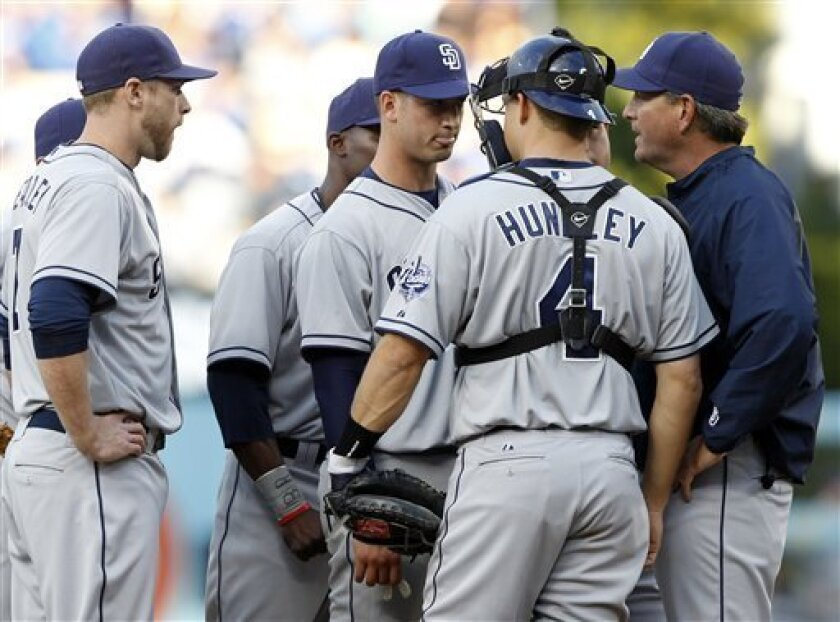 San Diego Padres starting pitcher Joe Wieland, third from right, gets a visit to the mound by the infield and pitching coach Darren Balsley, far right, after giving up two home runs and a double to the Los Angeles Dodgers during the first inning of their baseball game in Los Angeles, Saturday, Apri