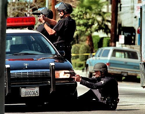 LAPD officers take shooting positions near the corner of Vanowen Street and Gentry Avenue on Feb. 28, 1997. Two suspects were killed while 10 officers and four bystanders were wounded.