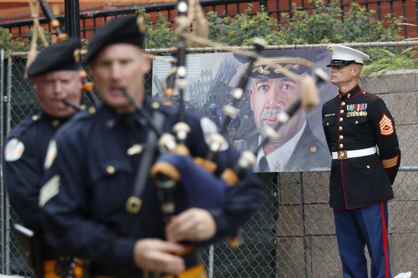 Un miembro del Cuerpo de Marines de Estados Unidos monta guardia junto a la imagen de un policía de Nueva York que murió durante los ataques terroristas del 11 de septiembre de 2001, mientras un grupo de gaiteros marcha durante el desfile en conmemoración del 15to aniversario de los ataques, el viernes 9 de septiembre de 2016, en Nueva York. (AP Foto/Mary Altaffer)
