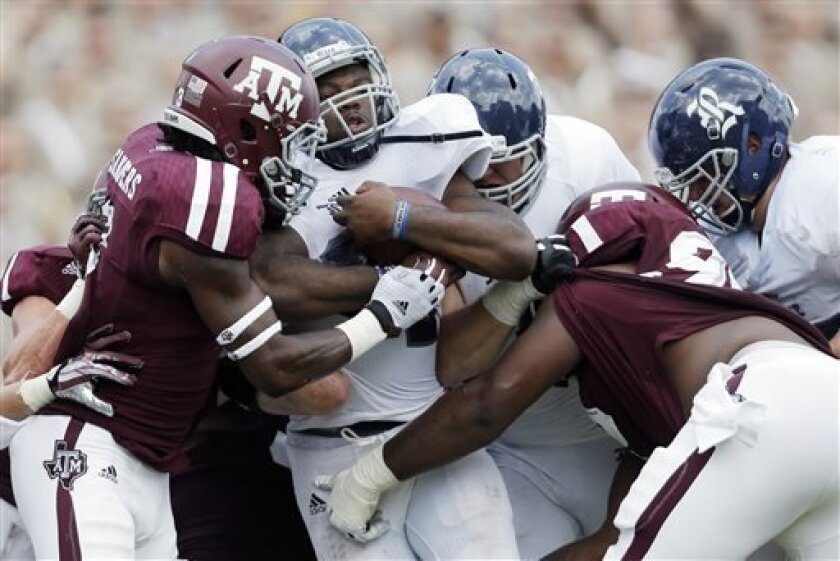 Rice's Charles Ross, center, is hit by Texas A&M defenders Tommy Sanders, left, and Isaiah Golden, right, as he works to cross the goal line for a touchdown during the fourth quarter of an NCAA college football game, Saturday,  Aug. 31, 2013, in College Station, Texas.  (AP Photo/Eric Gay)