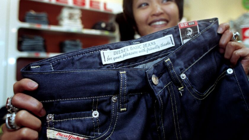 A sales clerk shows off a pair of Diesel jeans in 1997.