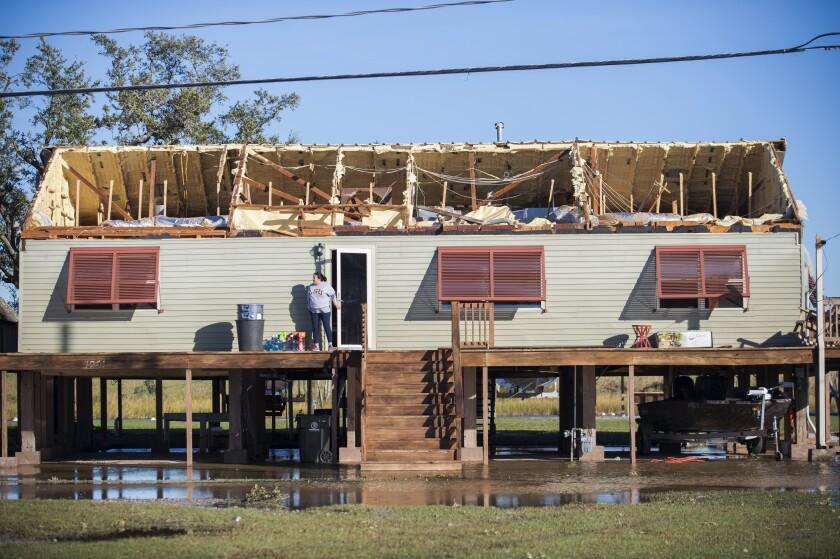A woman walks out of a house where the roof was torn away during Hurricane Zeta in Chauvin, La.