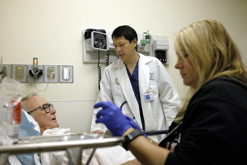 Dr. Ted Chan (center) and registered nurse Melissa Cayon insert an intravenous line in patient Dave Smith, 79, in the emergency department UC San Diego's Thornton Hospital Wednesday. The university is working with nonprofit West Health to conduct new geriatric research, and create a geriatric emerg