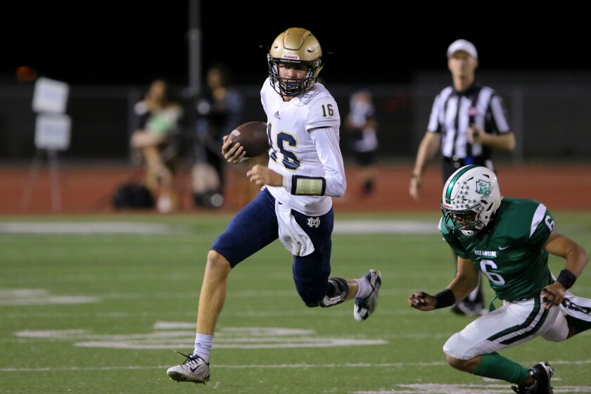 Mater Del Catholic quarterback Trevor Appelman carries the ball for a gain. Oceanside's #6 is Joseph Moreno.