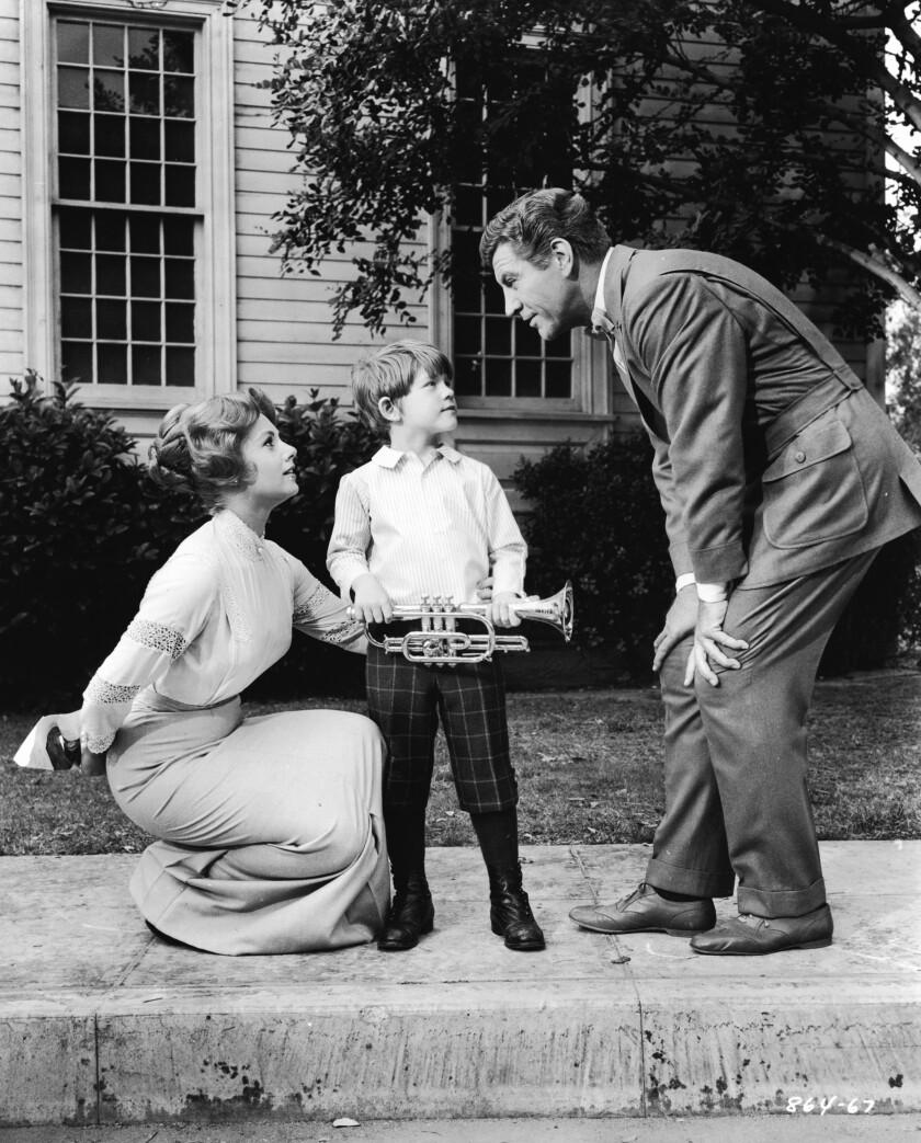 Un petit garçon tient une trompette tandis qu'une femme s'accroupit à côté de lui, à gauche, et un homme, à droite, se penche pour leur parler