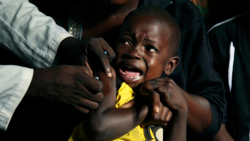 A boy reacts as he receives a yellow fever vaccine injection in the Kisenso district of Kinshasa.