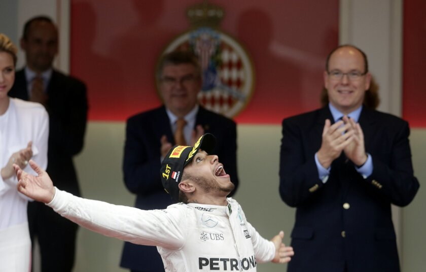 Mercedes driver Lewis Hamilton of Britain celebrates on the podium after winning the Monaco Formula One Grand Prix in Monaco, Sunday, May 29, 2016. (AP Photo/Petr David Josek)
